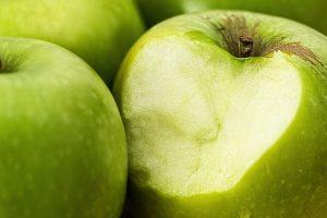 רופא חניכיים לטיפול בדלקת חניכיים בזמן אכילת תפוח ירוק