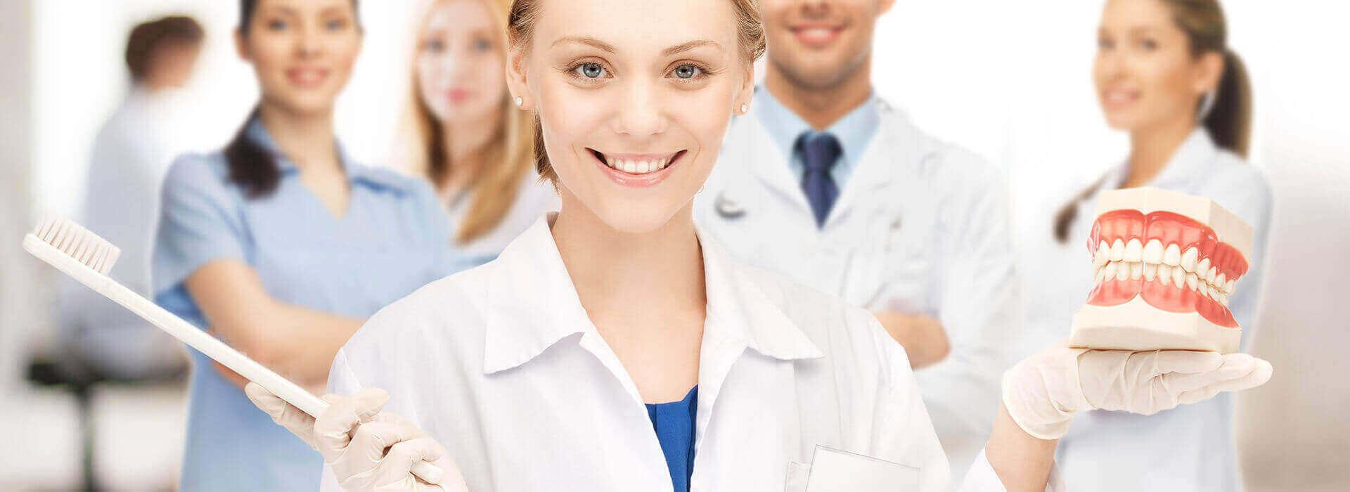 צוות הרופאים עם מברשת ושיניים תותבות במרפאת שיניים דנטאור